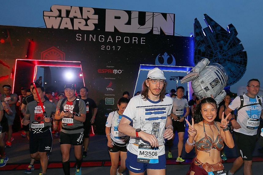 Runners decked out in an R2-D2 T-shirt and Princess Leia costume were among 15,000 who took part in the Star Wars Run at Marina Bay yesterday. The run was part of the Star Wars: May the Fourth Be With You Festival to celebrate the beloved movie franc
