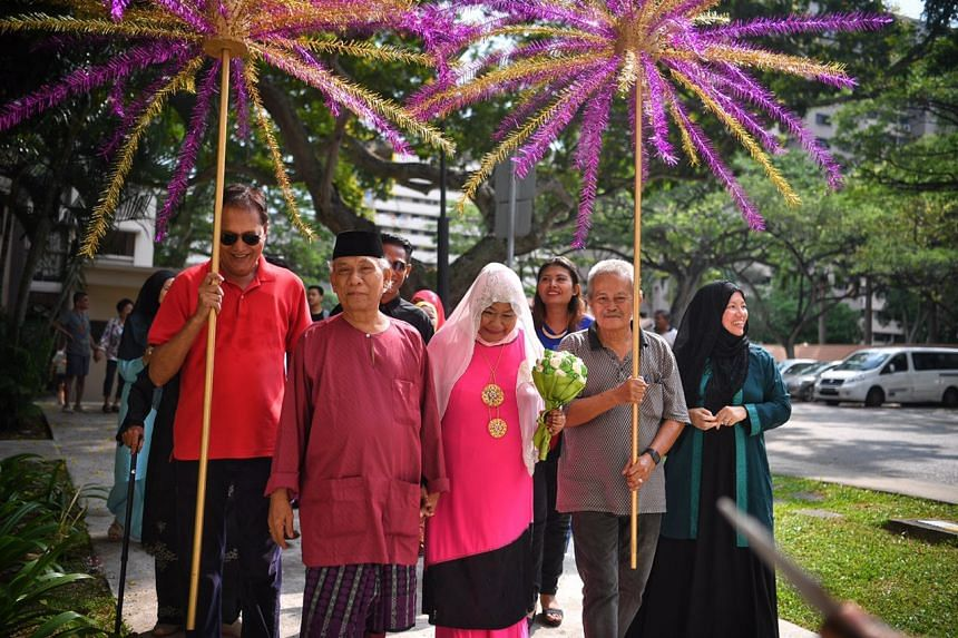 Mariah Abdul Hamid (centre-right), 70, and Ismail Sapuan, 62, hold hands as they walk to the Sunlove-Kampong Chai Chee Seniors Activity Centre after their solemnisation.