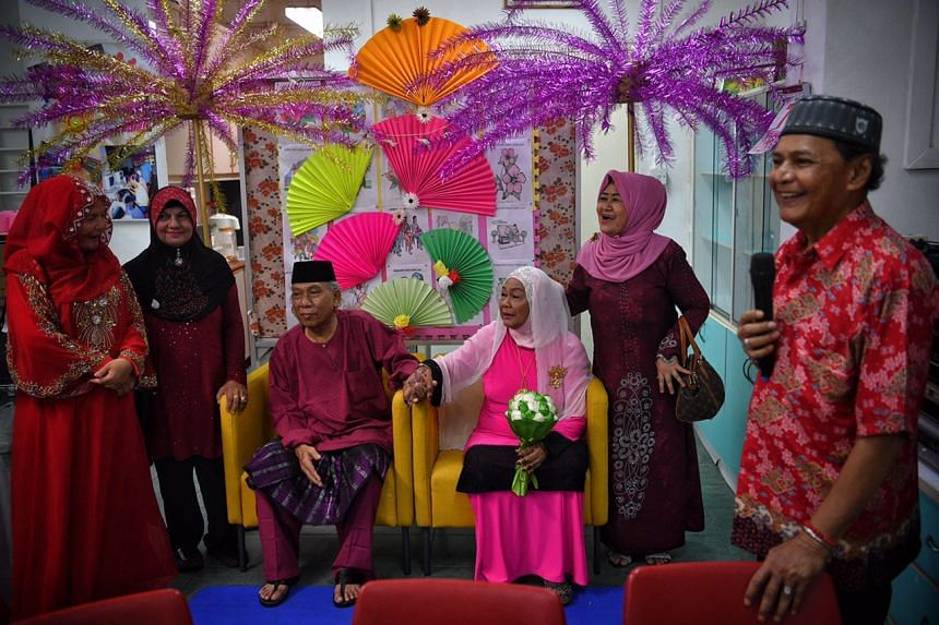 Newlyweds Mariah Abdul Hamid (centre-right), 70, and Ismail Sapuan, 62, hold hands as they take pictures with their friends (from left) Zainab Ismail, 58, Momin Jabar, 66 and Kamaria Hussein, 59, at the Sunlove-Kampong Chai Chee Seniors Activity Cent