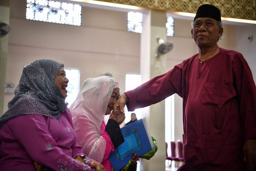 Newly weds Mariah Abdul Hamid (centre), 70, and Ismail Sapuan (right), 62, pictured after their solemnisation at Masjid Al- Ansar.