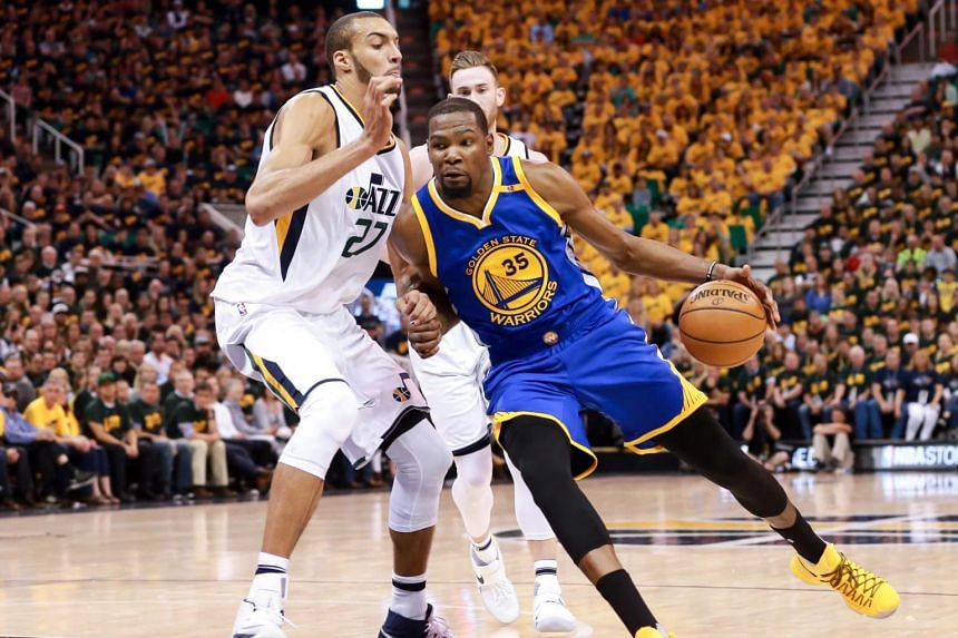 Golden State Warriors forward Kevin Durant (#35) driving against Utah Jazz centre Rudy Gobert (#27) during their NBA playoff match on May 6, 2017.