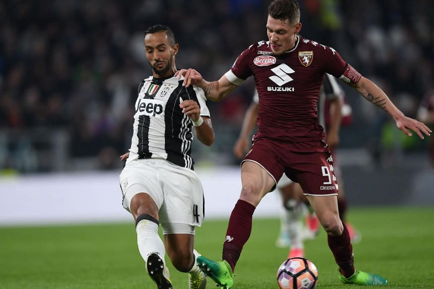 Juventus defender Medhi Benatia (left) vying for the ball with Torino forward Andrea Belotti during their match on May 6, 2017.