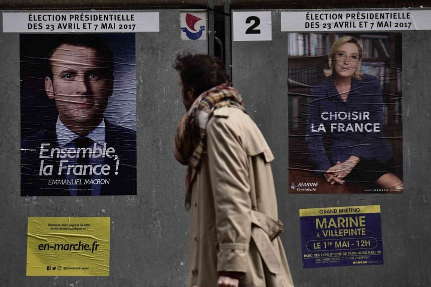 Posters of the two French presidential candidates on a sidewalk in Paris. France's presidential election commission yesterday advised the media not to publish details of Mr Macron's campaign e-mails which were leaked online, warning that publicat