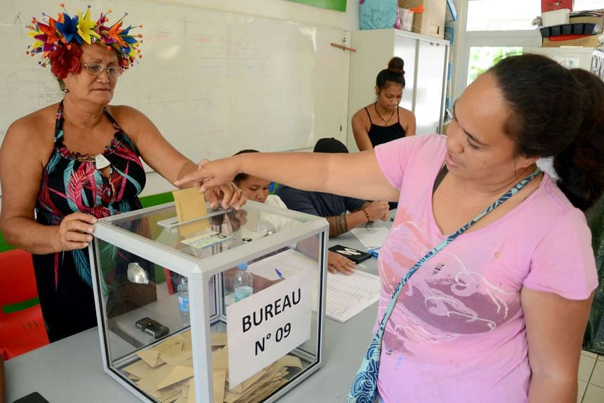 A woman casting her ballot at a polling station.