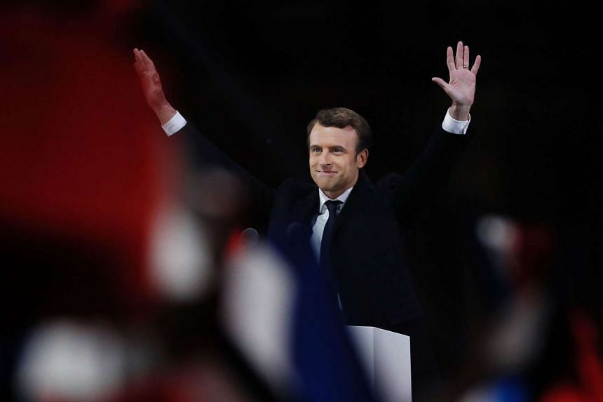 French president-elect Emmanuel Macron waves to the crowd as he delivers a speech at the Pyramid at the Louvre Museum in Paris on May 7, 2017.