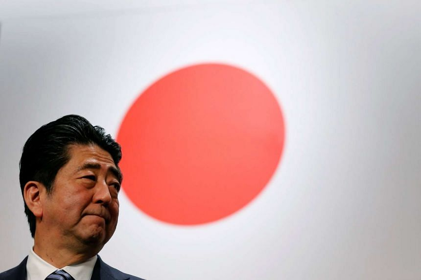 Japanese PM Shinzo Abe standing in front of the Japanese flag during the LDP's annual party convention in Tokyo on March 5, 2017.