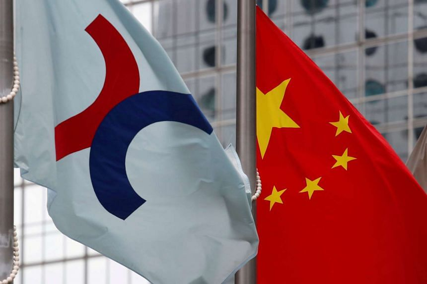 A Hong Kong Exchanges flag (left)  beside a Chinese national flag outside the Hong Kong Stock Exchange in Hong Kong.