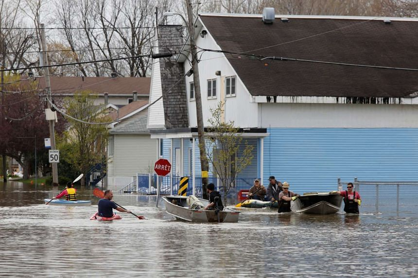 People using boats on a flooded residential street in Gatineau, Quebec, Canada.