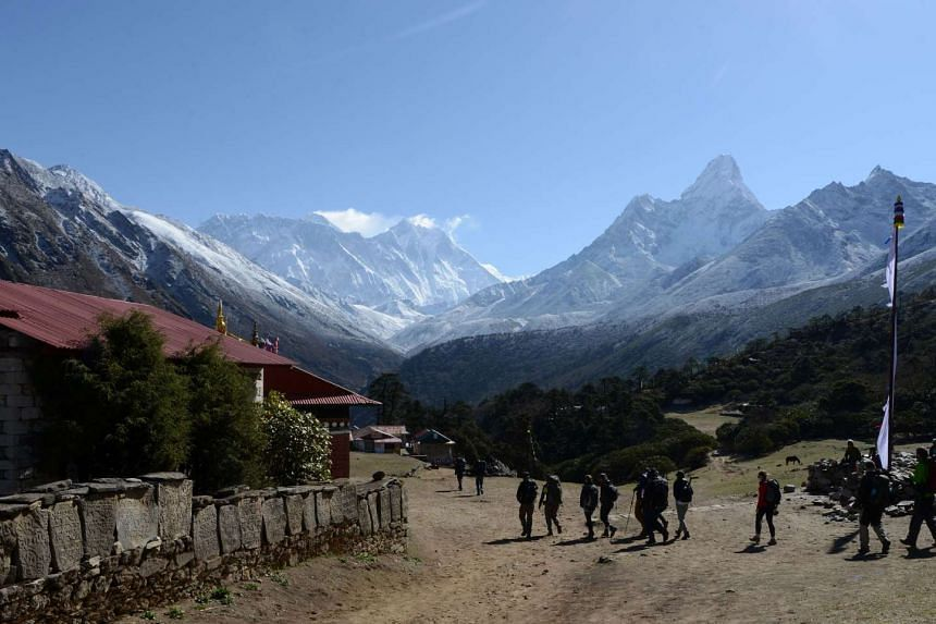 Trekkers walk in front of the Mount Everest range at Tengboche some 300kms north-east of Kathmandu on May 5, 2017.