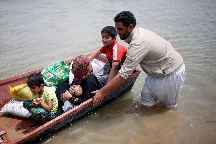 Displaced Iraqis crossing the Tigris River by boat in western Mosul, Iraq.