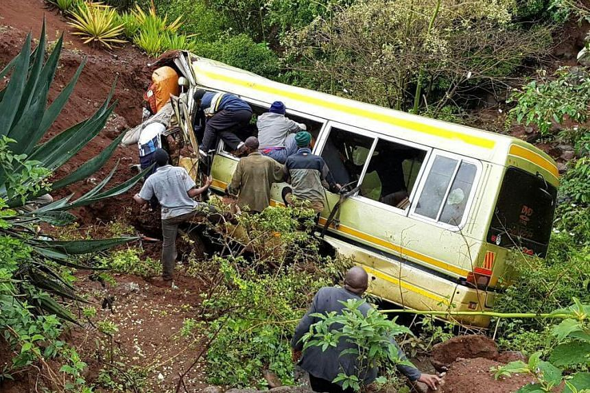 Residents attempt to rescue survivors at the scene of an accident at the Rhota village   in Tanzania's northern tourist region of Arusha, May 6, 2017.