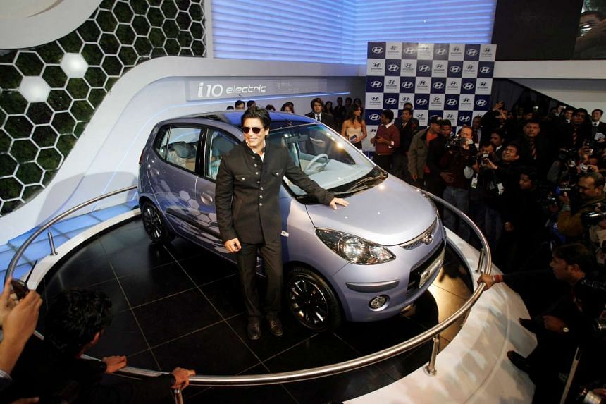 File photo of Bollywood actor Shah Rukh Khan with an electric car at India's Auto Expo in New Delhi.