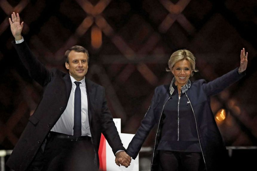 French President elect Emmanuel Macron and his wife Brigitte Trogneux celebrate on stage at his victory rally near the Louvre in Paris, France, on May 7, 2017.