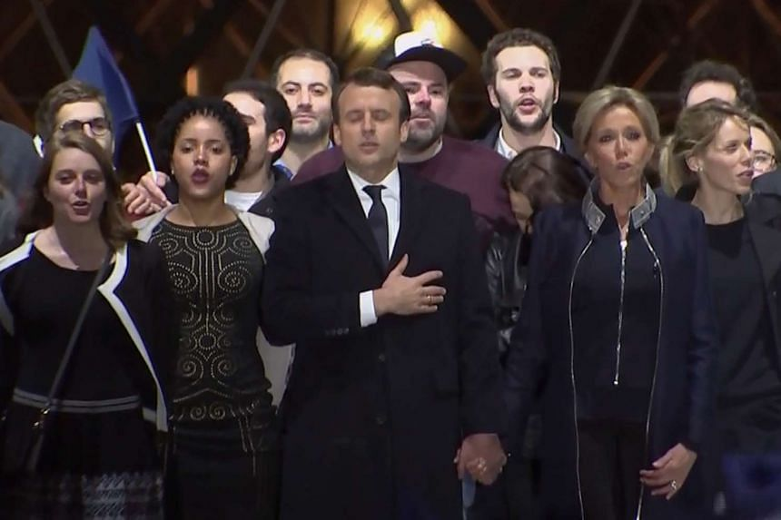 French president-elect Emmanuel Macron (centre) and his wife Brigitte Trogneux (second, right) singing the national anthem in front of the Pyramid at the Louvre Museum in Paris on May 7, 2017.