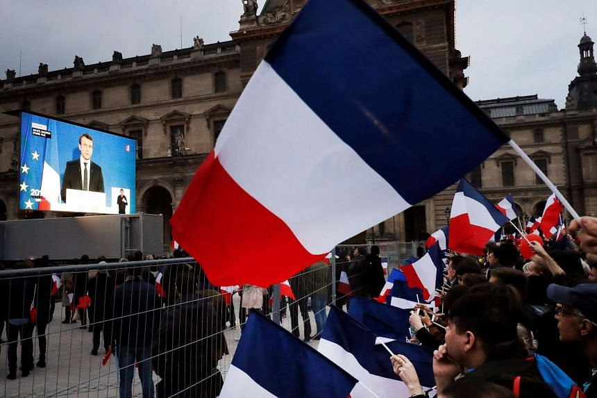 Supporters listen to French president-elect Emmanuel Macron as he delivers a speech at the Pyramid at the Louvre Museum in Paris on May 7, 2017.