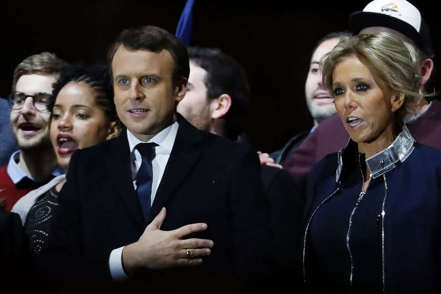 French president-elect Emmanuel Macron and his wife Brigitte sing the national anthem in front of the Louvre Museum's Pyramid on May 7, 2017.