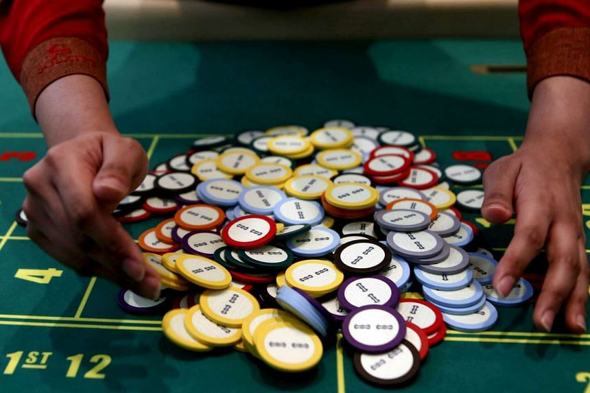 A casino dealer collecting chips at a roulette table in Pasay city, Metro Manila, Philippines.
