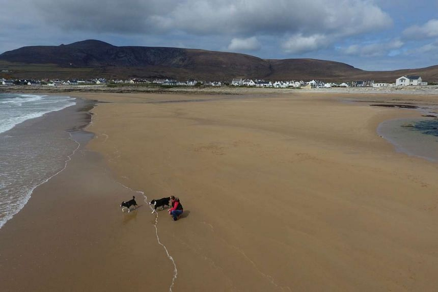 A woman walks her dogs along Dooagh beach on Achill island, County Mayo, Ireland, on May 5, 2017.
