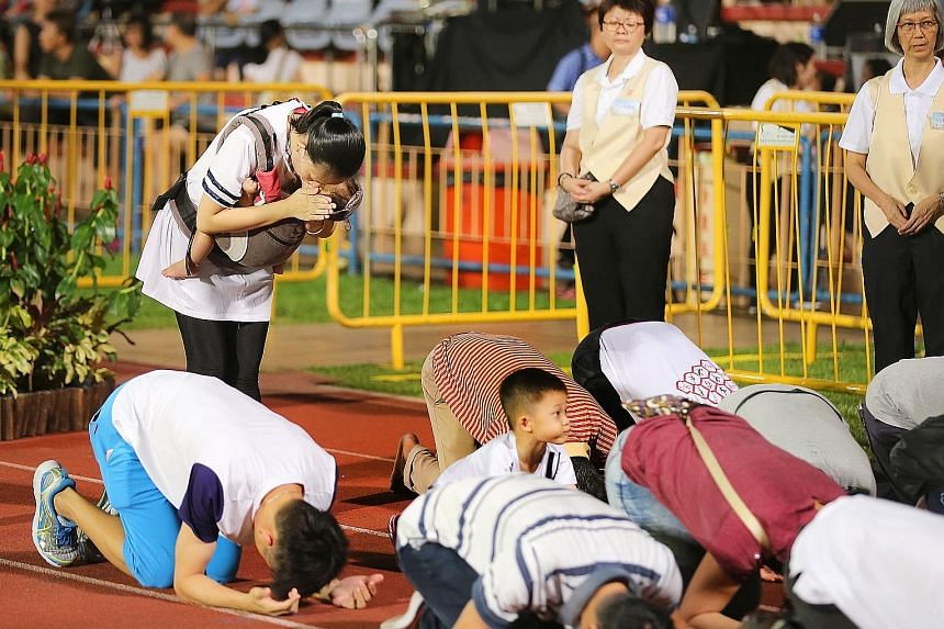 Above: Devotees lined Hougang Stadium's running track as they took three steps, knelt and bowed deeply with their foreheads touching the ground. Left: Ms Jaime Liao (standing), 32, and her son Lexuan (looking up), five, at the Vesak Day event. Minist