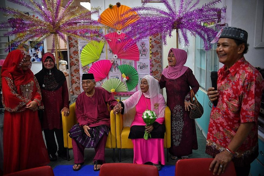 Newly-weds Mariah Abdul Hamid, 70, and Ismail Sapuan, 62, posing for photographs with their friends - (from left) Ms Zainab Ismail, 58, Ms Momin Jabar, 66, and Ms Kamaria Hussein, 59 - at the Sunlove Seniors Activity Centre in Chai Chee after the cou