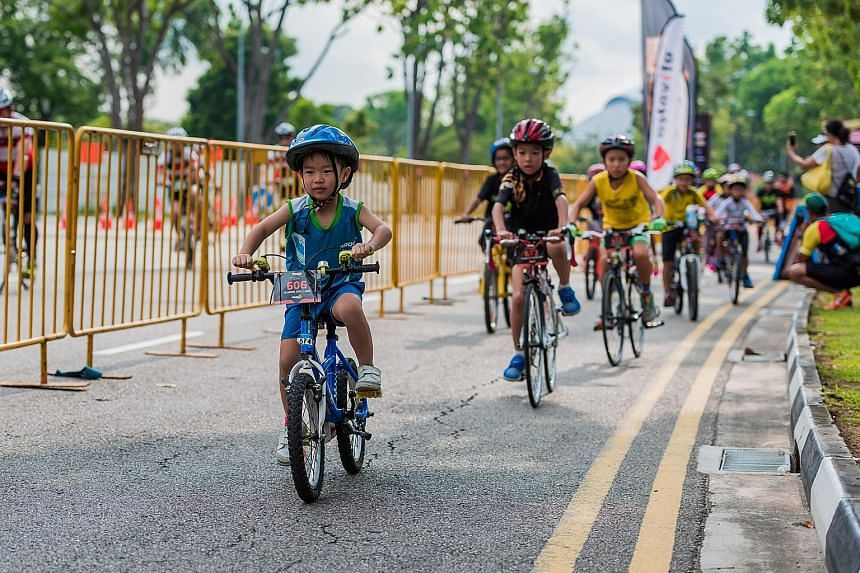 Seven-year-old Joel Liaw leading the way in yesterday's 5km introductory race in the Tri-Factor Bike & CycleRun Challenge. The nine-category event drew 1,285 participants to Nicoll Highway. David Strooper won the men's veterans' 49km bike race in 1hr