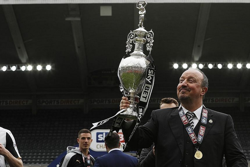 Newcastle manager Rafael Benitez celebrates winning the Championship trophy after his side finished a point above Brighton.