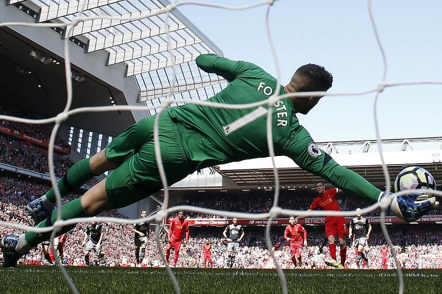 Southampton goalkeeper Fraser Forster dives to his right to keep out James Milner's penalty kick. Liverpool, who have failed to score against the Saints in four meetings this season, are third in the table with two games left.