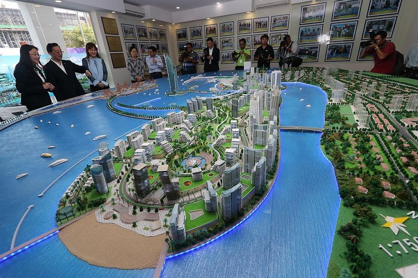 China's Ambassador to Malaysia Huang Huikang (second from left) checking out a model of the Melaka Gateway project with KAJ Developments CEO Michelle Ong (left) in March. Industry players and government officials are now doubtful about the project ta