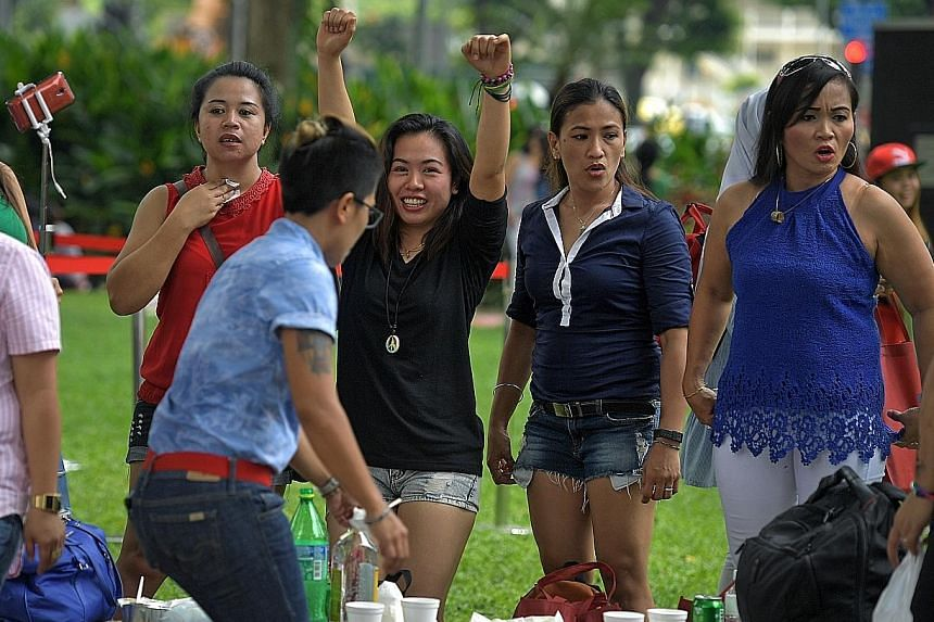 Maids at the labour movement's inaugural May Day celebration for them at Youth Park in Somerset yesterday. The minimum accident insurance coverage for maids will go up from $40,000 to $60,000 on Oct 1, and annual premiums are expected to go up by bet