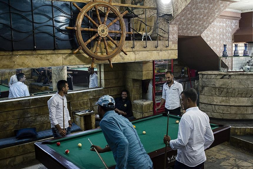 Locals playing pool recently at the Captain, a popular club in Mosul. ISIS had banned such activities as un-Islamic.