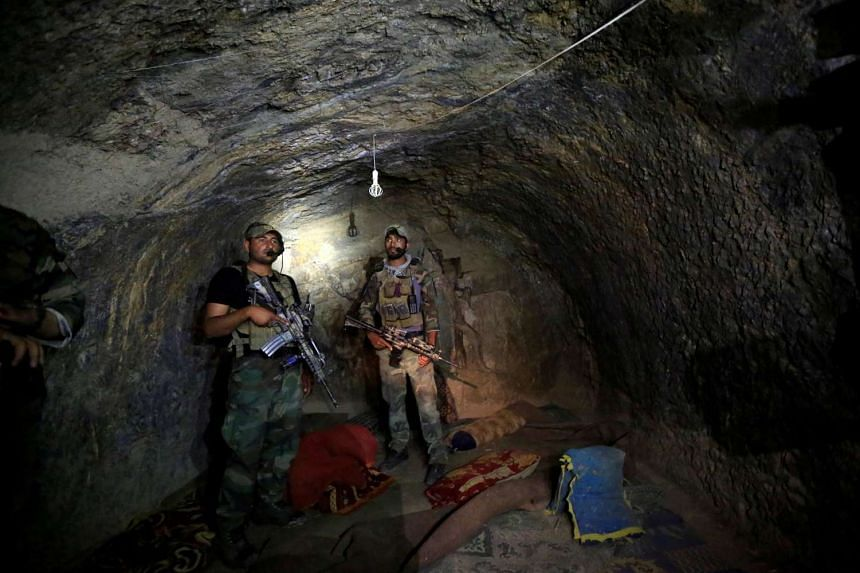 Afghan Special Forces inspect a cave used by suspected ISIS militants at the site where the US dropped a MOAB, or ''mother of all bombs' on April 23, 2017.