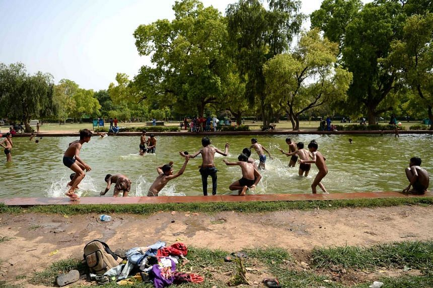 Indian children jump into a decorative pool in gardens at the India Gate monument on a hot iNew Delhi day.