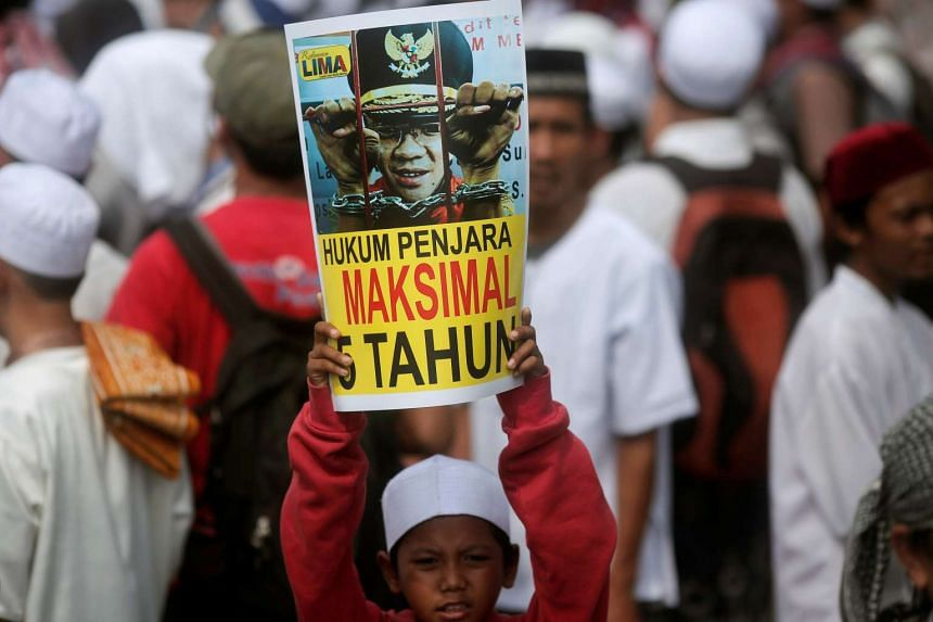 """A childs holds a poster calling for maximum punishment for outgoing Jakarta governor Basuki """"Ahok"""" Tjahaja Purnama ahead of the verdict of a blasphemy trial."""