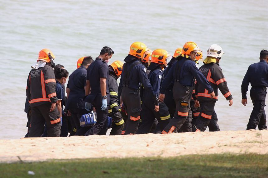 Police and SCDF personnel retrieve the body of the missing boy from the waters off East Coast beach on Monday (May 8) afternoon.