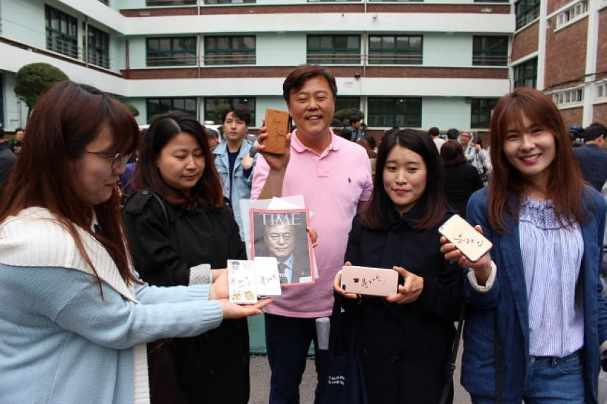 Supporters of Presidential candidate Moon Jae In holding out their smartphones and a magazine for Moon to sign, outside the polling station in Hongeun Middle School in Seoul.