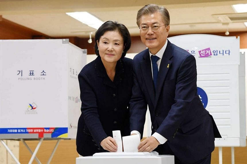Moon Jae In (right), presidential candidate of the Democratic Party of Korea (The Minjoo Party of Korea), and his wife Kim Jeong Suk cast their ballots at a polling site in Seoul.