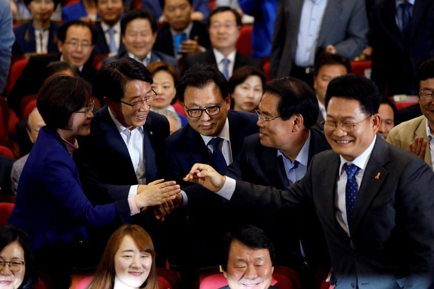 Party leaders and members of the Democratic Party of Korea react as they watch a television report on an exit poll of the presidential election in Seoul, South Korea on May 9, 2017.