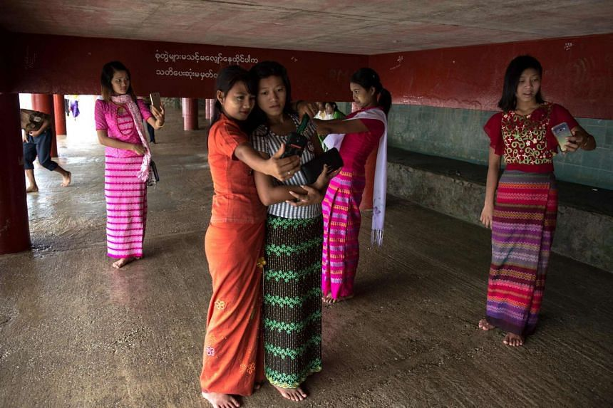 Women take selfies at the edge of the river underneath the Kyauktan Ye Le Pagoda in Myanmar on April 17, 2017.