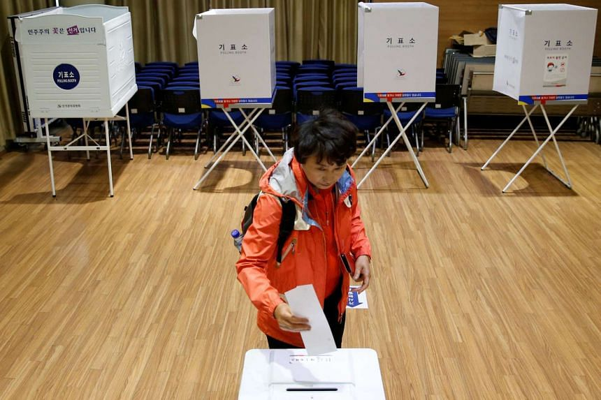 A woman casts her vote at a polling station during the presidential elections in Seoul, South Korea, on May 9, 2017.