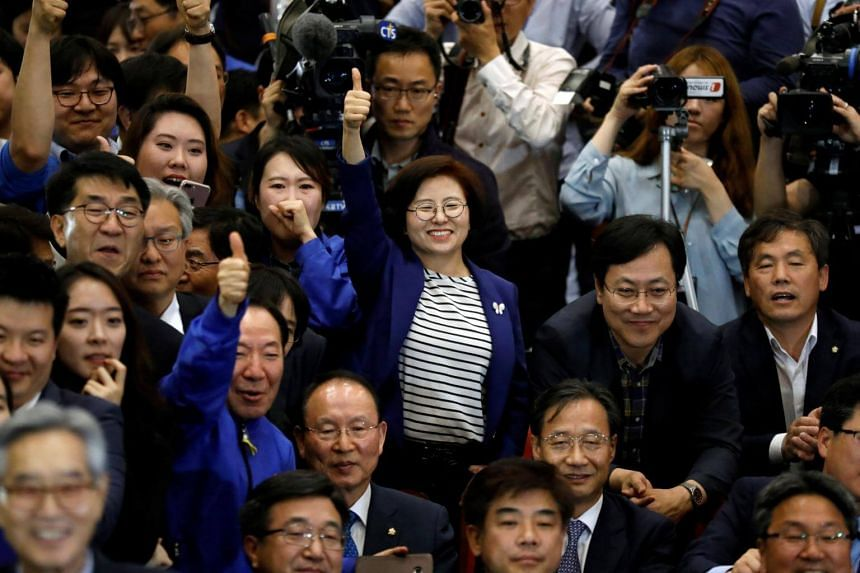 Party members of the Democratic Party of Korea react as they watch a television report on an exit poll of the presidential election in Seoul, South Korea on May 9, 2017.