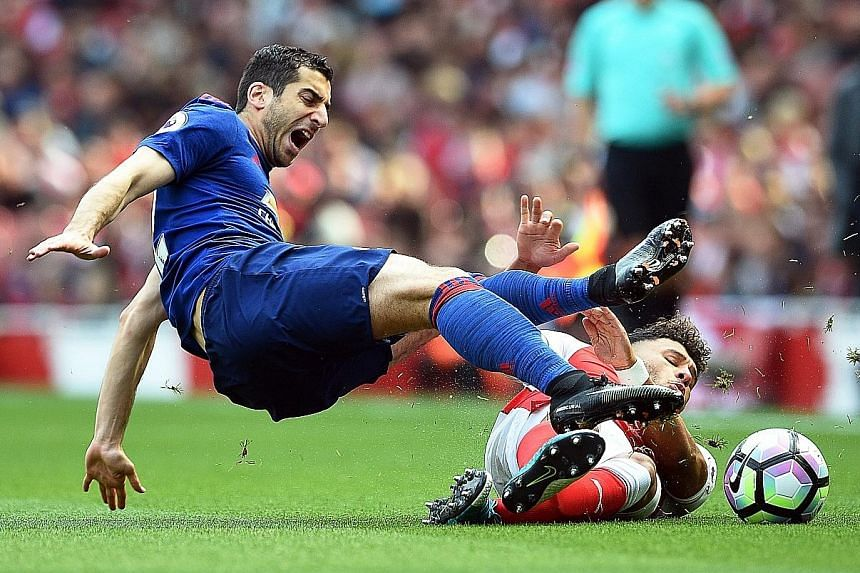 Manchester United's Henrikh Mkhitaryan (left) clashing with Arsenal's Alex Oxlade-Chamberlain during the Premier League match at the Emirates on Sunday. The match ended 2-0 in favour of the Gunners.