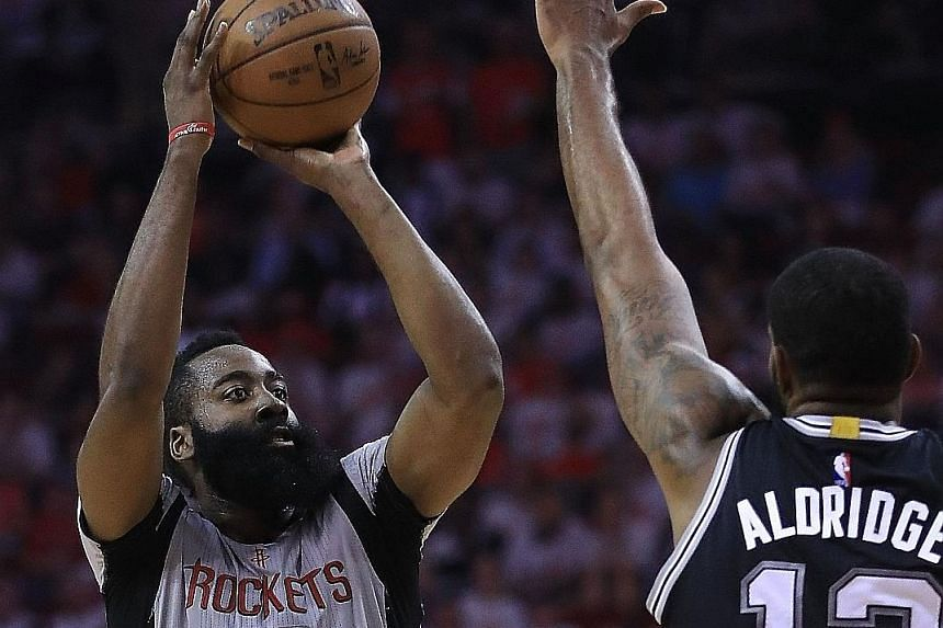 James Harden of the Houston Rockets shooting against LaMarcus Aldridge of the San Antonio Spurs. Harden scored 28 points as his team led from start to finish, with six of his team-mates also getting into double figures in the 125-104 win that tied th
