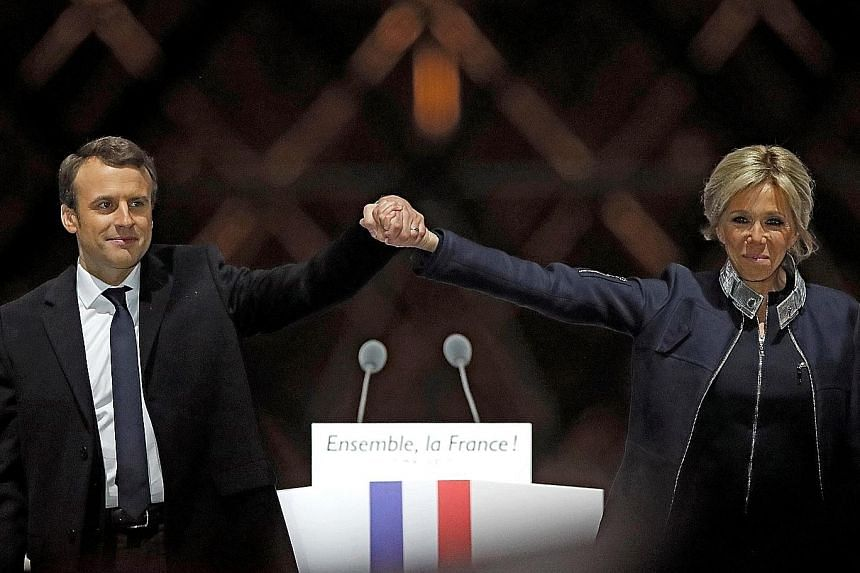Outgoing French President Francois Hollande (right) reaching out to President-elect Emmanuel Macron as they attended a ceremony to mark the end of World War II at the Tomb of the Unknown Soldier at the Arc de Triomphe in Paris yesterday. Above: Frenc
