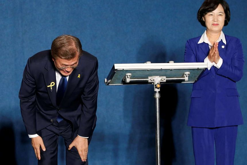 South Korea's president-elect Moon Jae In bowing to supporters next to Ms Choo Mi Ae, leader of the Democratic Party of Korea, at Gwanghwamun Square in Seoul on May 9, 2017.