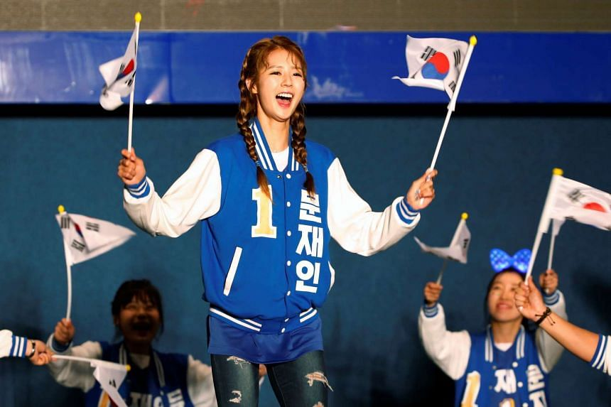 Supporters of presidential candidate Moon Jae In dancing at a live television broadcast of the presidential election exit polls result in Seoul on May 9, 2017.
