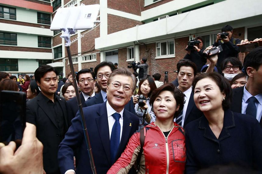 Mr Moon Jae In and his wife Kim Jung Sook  (right, take a selfie with a supporter.