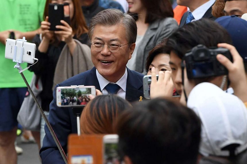 Mr Moon Jae In   takes selfies with supporters as he arrives at a polling station.
