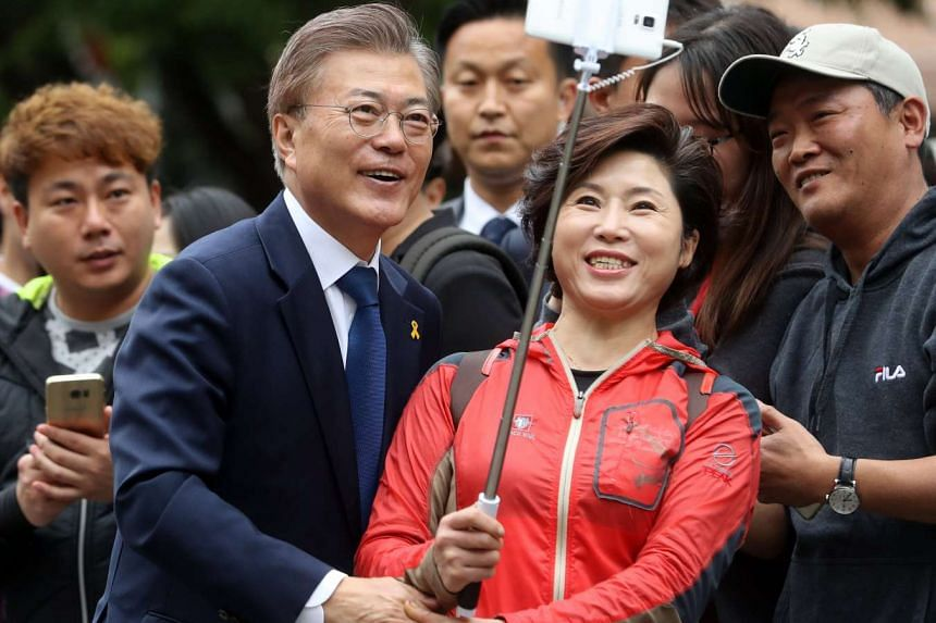 Mr Moon Jae In  poses  with citizens at a polling station.