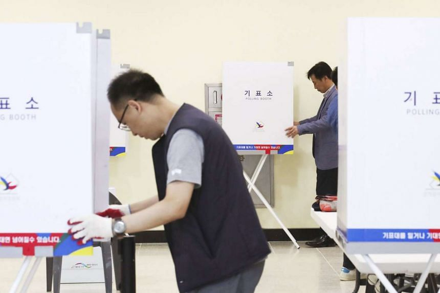 Staff of the Sejong City election committee set up polling booths at a community centre,