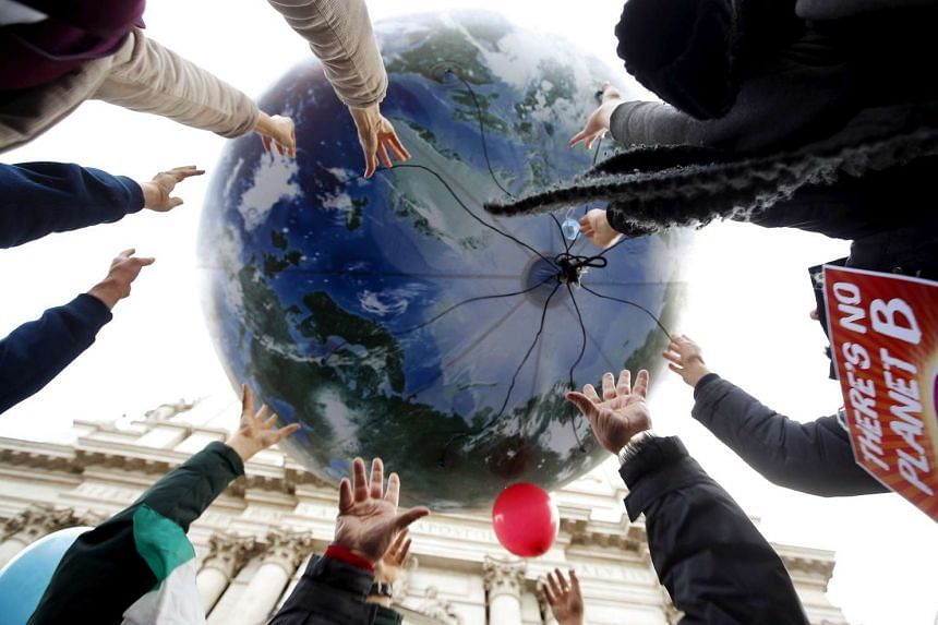 Protesters throw up a globe-shaped balloon during a rally held the day before the start of the 2015 Paris World Climate Change Conference in Rome, Italy, on Nov 29 2015.